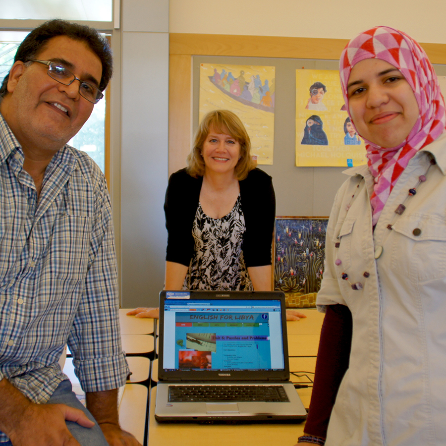 """Joy Egbert in between two Libyan graduate students, smiling. In the foreground is a laptop that says """"English for Libya."""""""